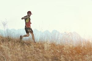 l'homme court en descente parmi les prairies de montagne d'automne photo