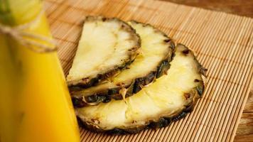 bouteilles de jus d'ananas sur une table en bois. photo