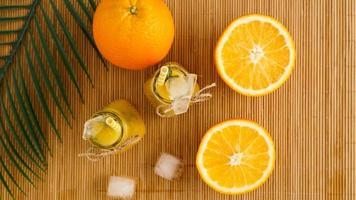 bouteilles de jus d'orange et pailles en papier. boisson glacée par une journée ensoleillée photo