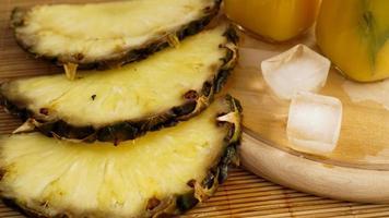 tranches d'ananas frais et glaçons sur un fond en bois photo