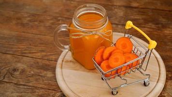jus de carotte frais avec chariot de supermarché et sur fond de bois photo