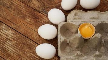 carton d'oeufs blancs et moitié d'oeuf fêlé avec vue de dessus de jaune photo
