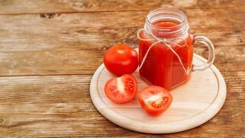 verre de jus de tomate sur table en bois. jus de tomate frais photo