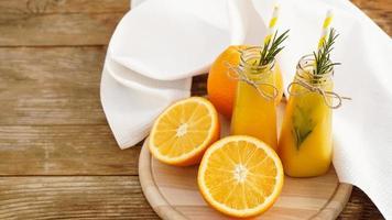 jus d'orange dans des bouteilles en verre. le jus est décoré photo