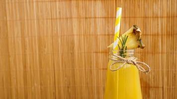 jus d'ananas dans une petite bouteille. des tranches d'ananas décorent la boisson photo
