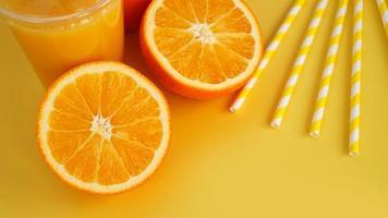 jus d'orange dans une tasse fermée de restauration rapide avec tube sur fond jaune photo