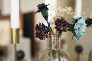 décoration intérieure de la maison. bocal en verre avec fleurs séchées, vase et bougie photo