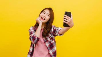 femme asiatique faisant une photo de selfie au téléphone avec une expression positive.