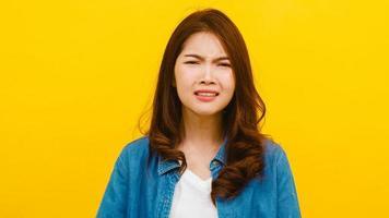 femme asiatique avec une expression négative sur fond jaune. photo