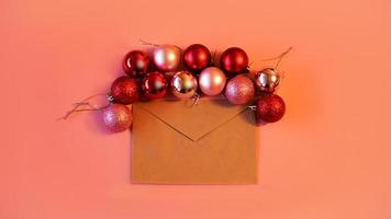 enveloppe de papier kraft avec des boules de noël rouges et roses sur rose photo