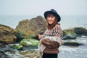 Portrait de jeune femme au chapeau sur un rocher contre une belle mer photo