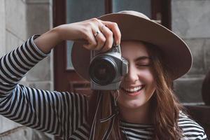 belle femme au chapeau prend une photo avec un appareil photo à l'ancienne