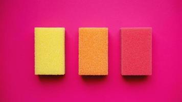 concept de nettoyage domestique. éponges colorées sur fond rose photo