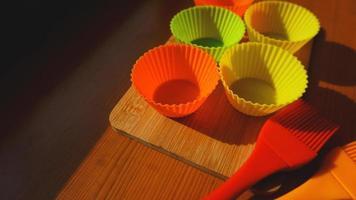 brosse en silicone et doublures de cupcakes sur table en bois photo