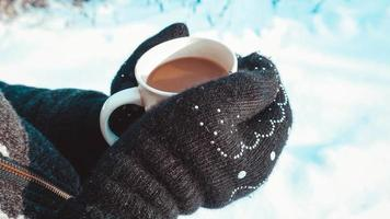 tasse chaude de café chaud réchauffant dans les mains d'une fille photo