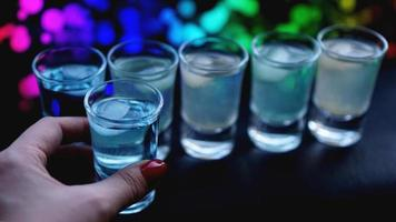 main féminine avec un coup d'alcool, arrière-plan flou néon photo