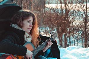 touriste femme assise sur une voiture et jouant de la guitare photo