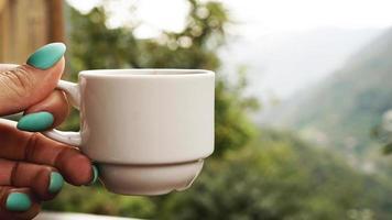 tasse blanche de café chaud à la main. le matin, vue froide sur la montagne photo