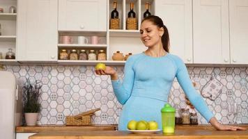 une belle femme dans la cuisine, souriante et tenant une pomme verte photo