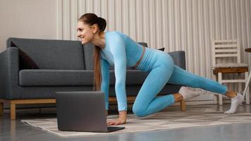 belle jeune femme faisant des exercices de remise en forme à la maison avec son ordinateur portable photo