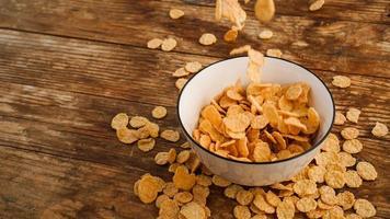 céréales tombant dans un bol blanc sur une table en bois photo