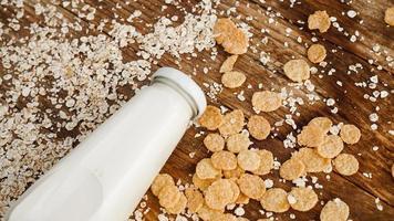 bouteille de lait frais sur fond de bois avec de l'avoine et des céréales photo