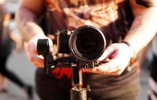 un homme avec un appareil photo et un objectif. photocaméra pour la prise de vue vidéo.