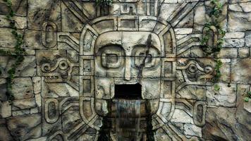 mur de pierre dans la jungle. masque de tête et cascade de la bouche photo