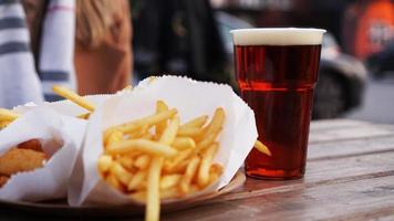 bière brune et frites sur une table en bois. aire de restauration. nourriture à emporter photo