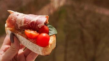 main de femme avec bruschetta de tomates cerises. apéritif de vin italien photo