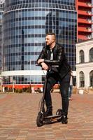 transports innovants. Heureux gars optimiste s'appuyant sur un scooter électrique photo