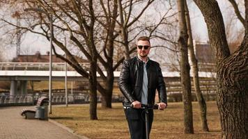 jeune homme dans une veste noire et des lunettes de soleil monte un scooter électronique photo
