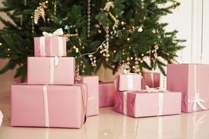 coffrets cadeaux roses avec des rubans sous le sapin de noël photo