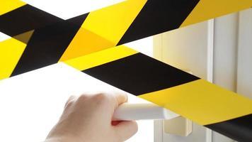 le ruban jaune du coronavirus reste à la maison. une main atteint la poignée de porte photo