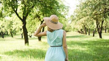 Jeune femme au chapeau de paille dans le jardin ensoleillé photo