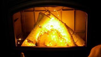 pile de bois de chauffage et guirlande sur fond clair, vue rapprochée photo