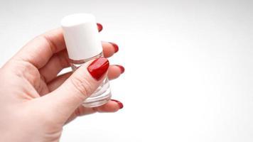 une fille aux ongles rouges tient un vernis transparent ou de l'huile pour cuticules photo