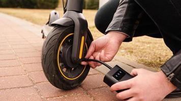 un homme pompe de l'air dans la roue d'un scooter électrique photo