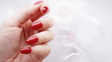 belle main féminine avec des ongles rouges contre le bouquet de mariage photo