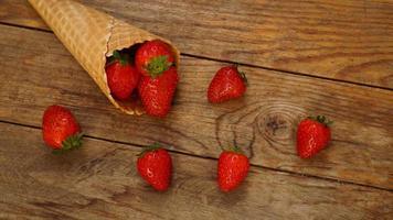 cornet de crème glacée aux fraises sur un fond en bois photo