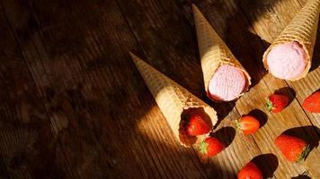 glace à la fraise dans un cornet gaufré. fruits rouges et boules de glace photo