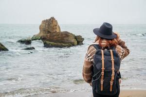 femme au chapeau et avec sac à dos sur la plage sur fond de mer photo