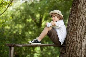 garçon est assis sur un banc photo