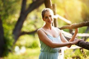 jeune jolie femme se tient près de la haie dans le jardin photo