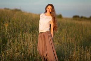 belle femme aux cheveux longs dans une jupe et un chemisier blanc photo