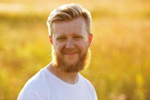 homme souriant avec une grande barbe rousse photo