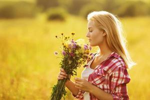 fille heureuse avec un bouquet de fleurs sauvages photo