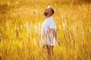 l'homme heureux se tient parmi l'herbe des prés photo