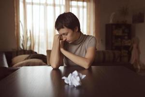 une femme très triste est assise devant une lettre froissée photo