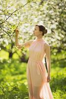 Femme debout près du pommier en fleurs photo